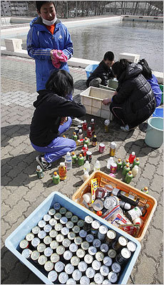 Children washed plastic bottles and cans of at a makeshift shelter in Hirota in northern Japan on Friday.