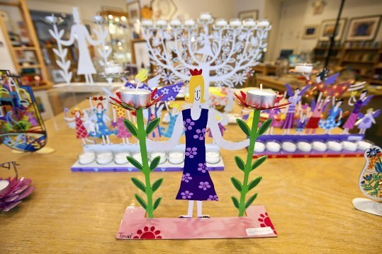 "Yet over time Kolbo introduced candlesticks, Passover plates, and ritual wine glasses that were artistic and cutting edge in design. ""We had to educate people that it was OK to have these beautiful objects in their homes,"" he said. Colorful menorahs at Kolbo Fine Judaica."