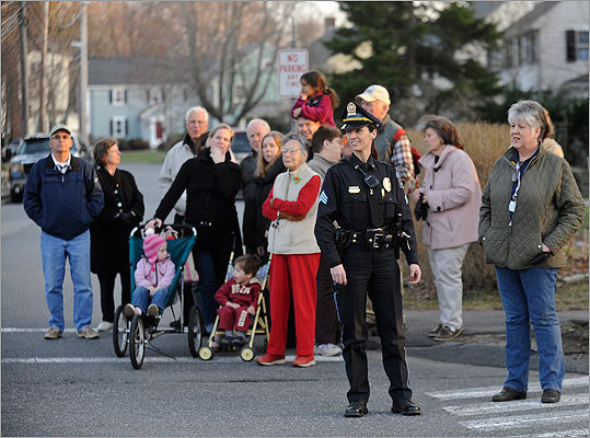 A police officer stood with residents who gathered to watch the big move.