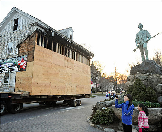 The house was rolled past the Minuteman statue at Lexington's Battle Green.