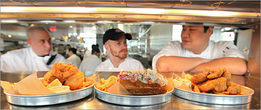 Dishes of a Fisherman's Trio, lobster roll, and fish & chips wait to be picked up after being prepared by the kitchen staff, which includes area chef Chris Cowen (left), kitchen manager Justin MacDonald (center), and certified trainer T Pham.