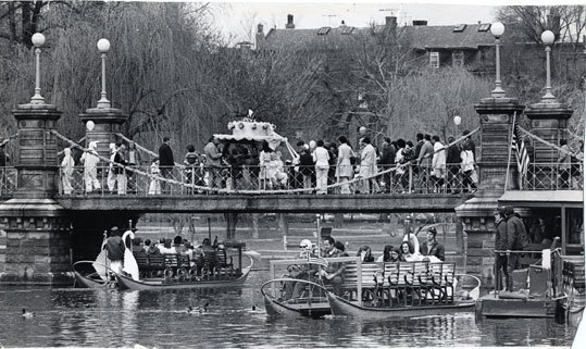 April 15, 1974 A busy day in Public Garden with the Swan Boats running, and an Easter cake on top of the bridge