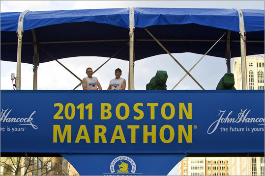 Runner Justin Garofano (left) and friend Joe Sobalo of Billerica posed for photos after sneaking up to the media bridge above the finish line on Boylston Street on Sunday.