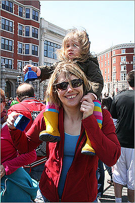 Licia Rochier, 2, of Montreal, had a lofty perch on friend Nancy DaSilva's shoulders, as they waited for Licia's father Loic to arrive in Kenmore Square.