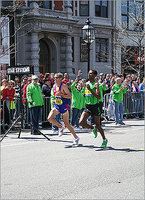 American Ryan Hall and Ethiopian Gebregziabher Gebremariam passed the '1 mile to go' sign.