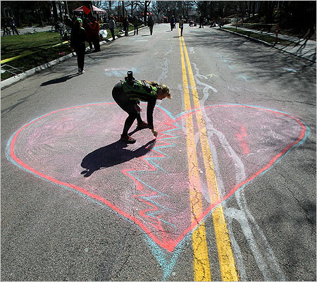 Lauren Hefferon put the finishing touches on a giant heart on the Comonwealth Avenue pavement at Heartbreak Hill in Newton.
