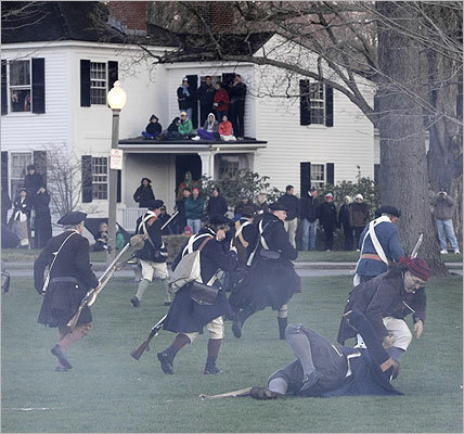 Garbed in 18th-century attire, reenactors brought history to life on Monday as they recreated the scene at the Battle of Lexington on April 19, 1775. Read on to see scenes from the Lexington Green. In this photo, spectators got a front row seat in history from the roof of a porch next to Lexington Green as they watched the Minutemen get fired upon by the British during the Patriots Day reenactment on Lexington Green.