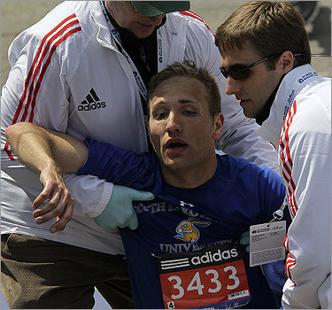 An exhausted runner is helped back to his feet after the race.