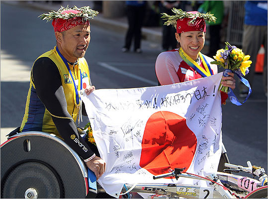 Masazumi Soejima (left) and Wakako Tsuchida held a flag from their native Japan together after their victories in the wheelchair races.