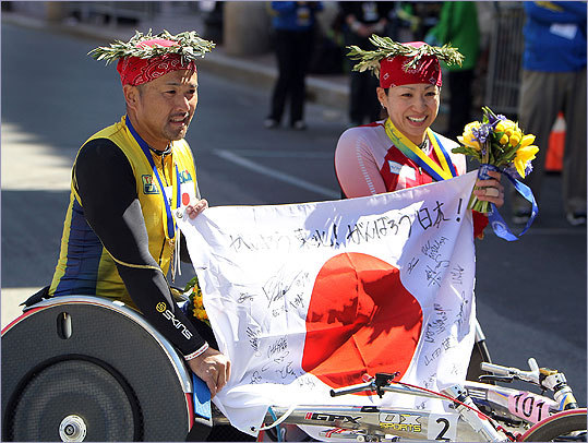 Wheelchair winners Masazumi Soejima (left) and Wakako Tsuchida, both from Japan, show off their country's flag at the finish line.