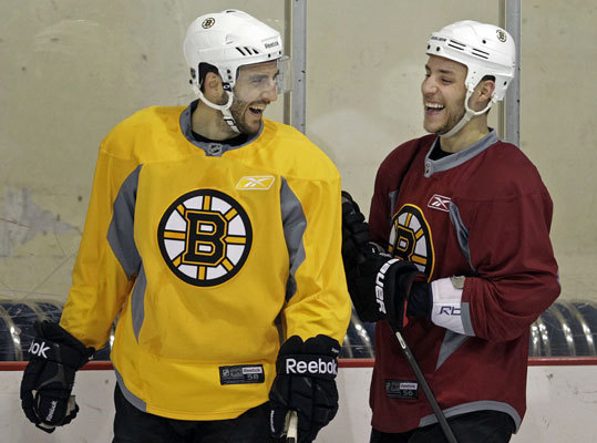 Patrice Bergeron (left) and teammate Gregory Campbell (right) have a laugh together during Wednesday's workout.