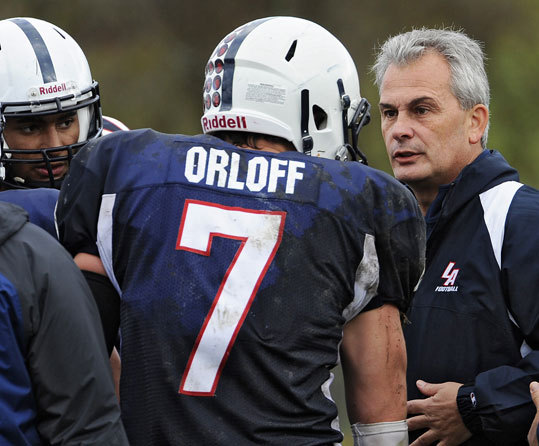 Lawrence Academy's former football coach Mike Taylor confers with quarterback Michael Orloff during a game against Belmont Hill School.
