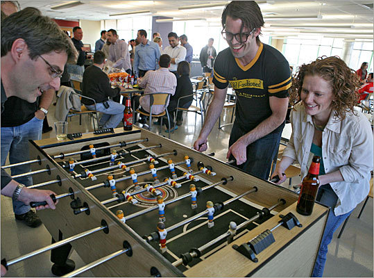 Nowadays, it has become less of a social hour and more of a beer bash. Every week, the employees gather to partake in conversation and leisurely enjoyment. Here, from left, Mark Namchuck, Charles Jurkiewicz, and Hailet Harris play foozeball.