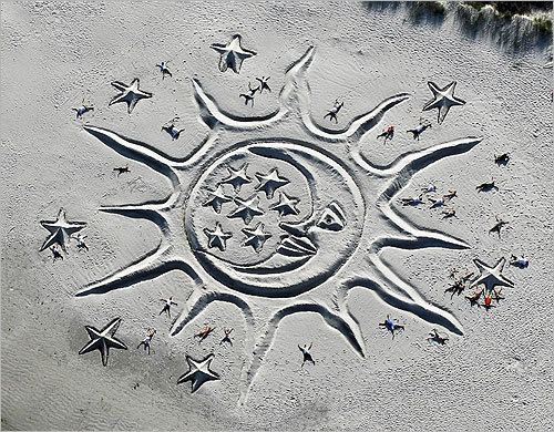 Volunteers lay in a sand sculpture created by artist Todd Brittingham titled 'Sun and the Moon' at Jetty Park in Cape Canaveral, Fla., on Sunday. The sculpture is dedicated to the ending of the space shuttle program, and the stars are dedicated to the lost space shuttle astronauts.