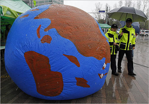 South Korea Police officers walked past a balloon shaped like a globe while environmental activists to mark Earth Day at the Seoul City Hall plaza in South Korea on Friday.