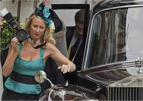 An unidentified photographer adorned with a playful headpiece shot pictures before the wedding as Kate Middleton was helped out of a Rolls-Royce.
