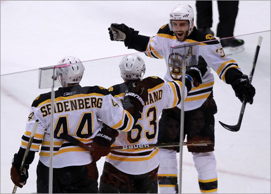 Center Patrice Bergeron (right) was all smiles after Brad Marchand (center) tied the score at 2-2 during the first period.