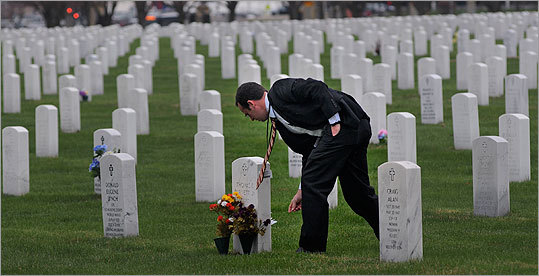 Jim Schweizer, assistant to the director of Fort Snelling National Cemetery, straightened flowers at the grave of Thomas Burnett in Bloomington, Minn. Burnett died Sept, 11, 2001, along with 39 other passengers and crew when Flight 93 was hijacked and crashed into a field near Shanksville, Pa., while flying to San Francisco from Newark, N.J.