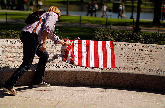 Antonia Bellanca gently moved a flag to look at the names of victims etched on the Public Garden memorial.