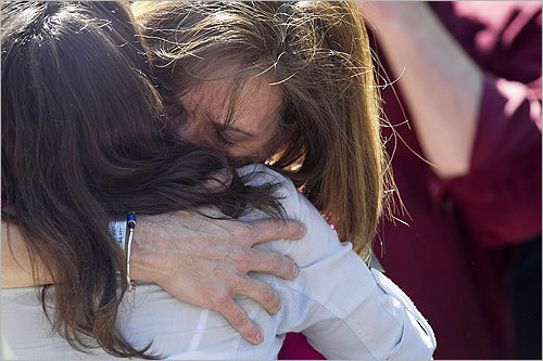 Before the moment of silence, Christie Coombs, who lost her husband Jeff Coombs, hugged Carie Lemack, in white, who lost her mother Judy Larocque.