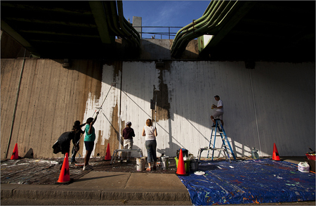 Work on a long-delayed community mural at the Orange Line overpass on Route 60 has begun.