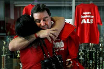 Paul Seaver gets a hug from sister-in-law Lori Maffia during charity games to support ALS research and the former coach.