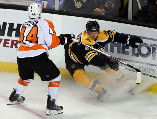 Bruins defenseman Dennis Seidenberg and Flyers defenseman Kimmo Timonen chased after a loose puck in the corner in the first period.