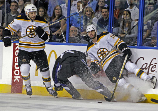 Nathan Horton (right) took out Tampa Bay's Simon Gagne, allowing Milan Lucic (left) to pick up the puck and start a rush in the first period.