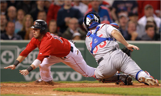 Red Sox second baseman Dustin Pedroia dove around the tag of Cubs catcher Koyie Hill to score on a sacrifice fly by Kevin Youkilis and give the Red Sox a 3-2 lead.