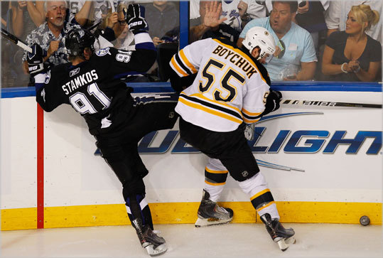 Johnny Boychuk (55) of the Bruins checks the Lightning's Steven Stamkos.