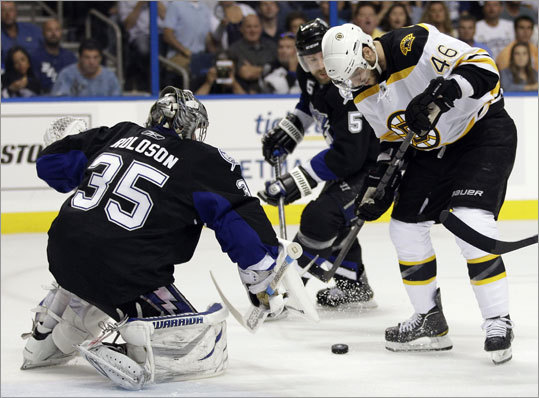 Bruins center David Krejci made a bid for the puck in front of Lightning goalie Dwayne Roloson in the first period.
