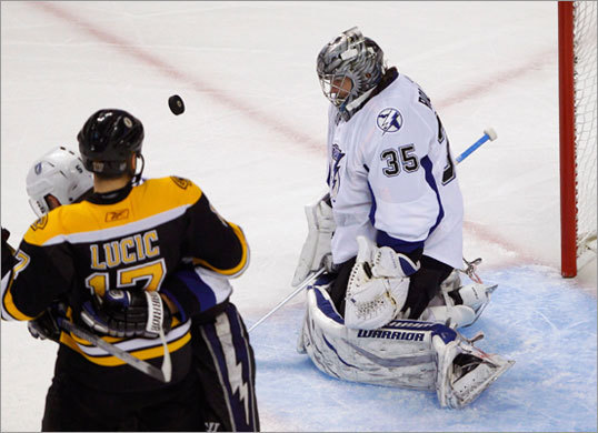 Lightning goalie Dwayne Roloson (right) made a save as Boston Bruins left winger Milan Lucic looked on.