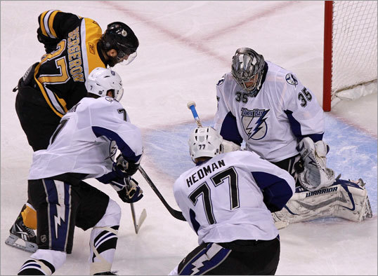 Tampa Bay goalie Dwayne Roloson (right) made a glove save on this shot by Boston Bruins center Patrice Bergeron (37) during the first period.