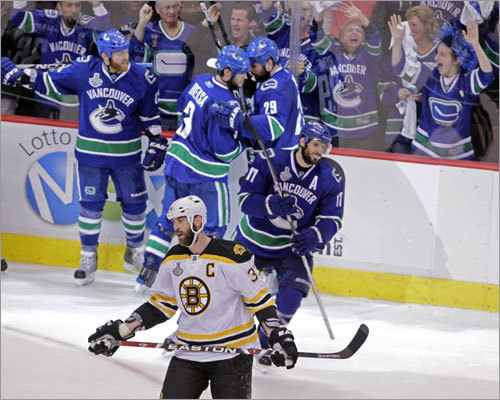 Bruins defenseman Zdeno Chara didn't care to watch as the Canucks, including game-winning goal scorer Raffi Torres (left, with beard), celebrated taking a 1-0 lead in the final minute.