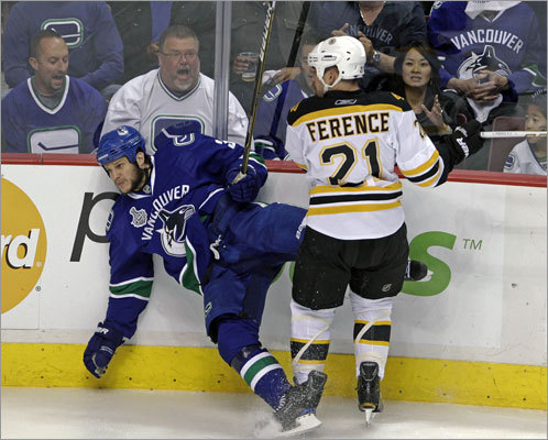 The Canucks' Kevin Bieksa hit the ice after a first-period hit by the Bruins' Andrew Ference.