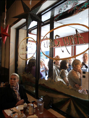 A patron of Amy Ruth's, 113 W 116th St in Harlem, takes in the ambiance of the iconic Halrem eatery as other patros wait outside. Read: Harlem makes a visitor feel its forward movement