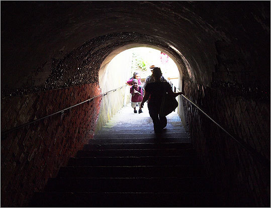 Island visitors make their way through one of Fort Warren's several dark staircases and corridors. No lighting has been added to the fort, so visitors may want to bring a flashlight.