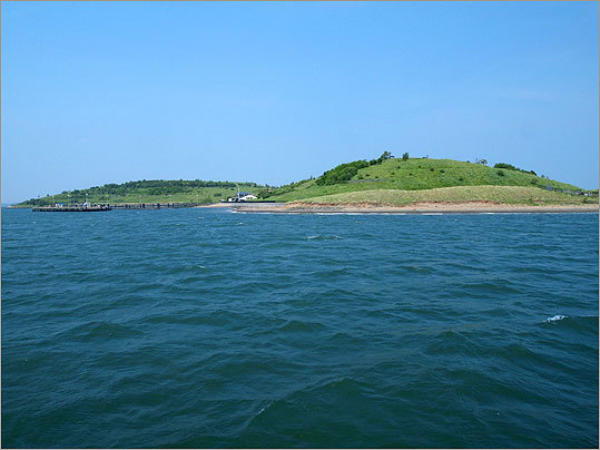 A view of Spectacle Island from an approaching ferry shows the island's South Drumlin at right and North Drumlin at left. Though the shape has been drastically altered by human interference, the island maintains the general form that to early colonists resembled a pair of eyeglasses and inspired its name.