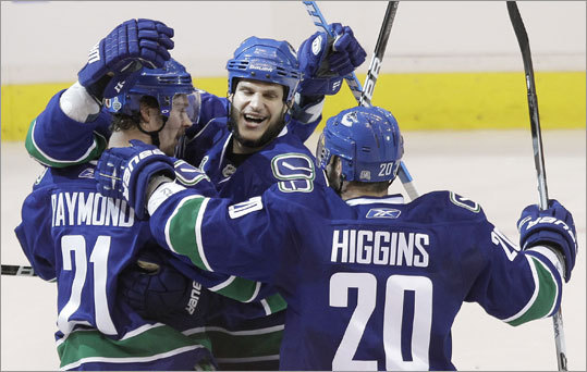 The Canucks drew first blood in Game 2 of the Stanley Cup Final when Alexandre Burrows (rear, mostly obscured) scored on a wrist shot at 12:12 of the first period. Canucks Mason Raymond, Kevin Bieksa and Chris Higgins (from left) celebrated with Burrows.