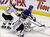 Vancouver's Alex Burrows swings around the Bruins' net en route to his winning goal