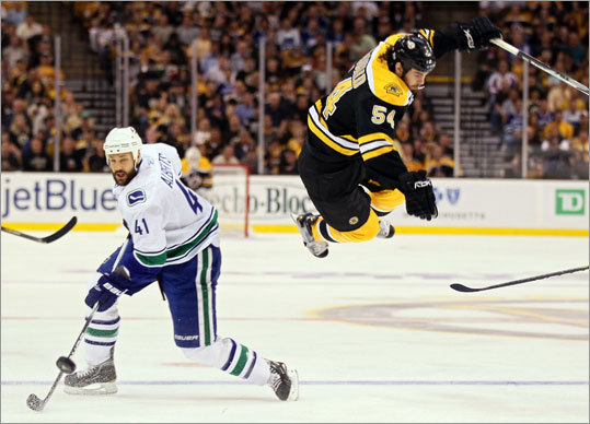 Bruin Adam McQuaid was sent flying after being checked by Canuck Andrew Alberts in the first period.