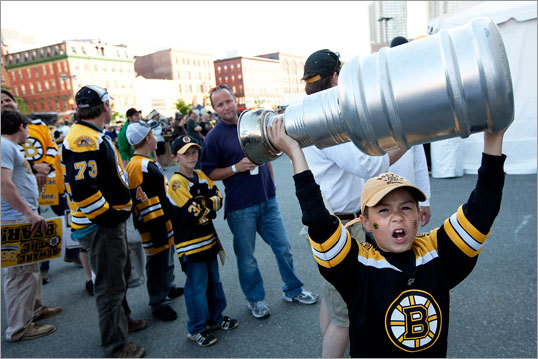 Eight-year-old Ryan Packer of Wilmington help up a homemade Stanley Cup outside of TD Garden before Game 3 of the Stanley Cup Finals between the Bruins and Canucks.