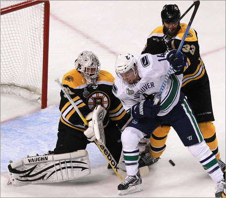 Bruins goalie Tim Thomas defenseman Zdeno Chara teamed up to take out Canucks left wing Alex Burrows in front of the goal in the first period.