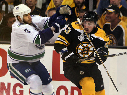 Bruins forward Brad Marchand took a stick across the face from Vancouver's Kevin Bieksa in the first period.