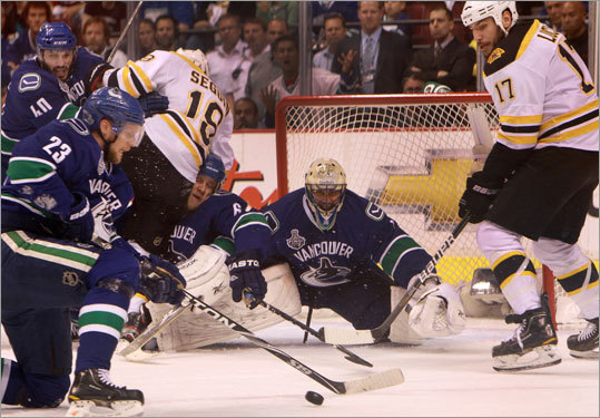 As chaos ensued around him, Canucks goalie Roberto Luongo kept his eye on the puck in the first period of Game 5 of the Stanley Cup Final. Bruins center Tyler Seguin (19) and left wing Milan Lucic (17) fought a host of Canucks in front of the goal.