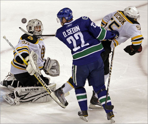 The Canucks' Daniel Sedin was unable to hit a flying puck past Bruins goalie Tim Thomas in the first period. Johnny Boychuk (right) helped out.
