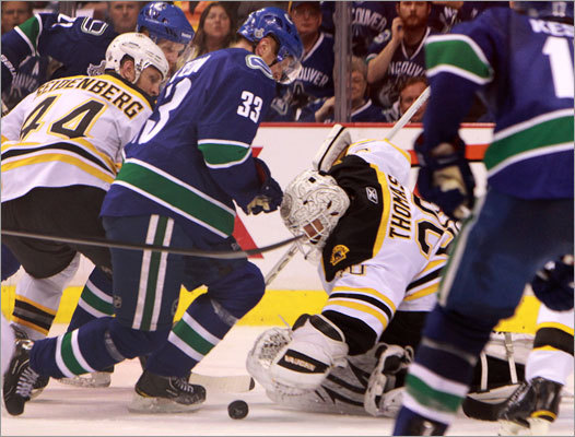 Bruins goalie Tim Thomas (30) mades a glove save in front of Canucks center Henrik Sedin during the second period.