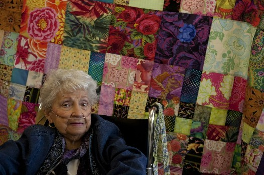 It has been decades, a half-century even, since these women had young children. Many of them now are grandmothers, some great-grandmothers. But the women in the Friday morning quilting club at Belmont's Beech Street Center have spent the last few months creating colorful covers for kindergartners who live half a world away. Genevieve Priest sits in front of a quilt she made at the Beech Street Center quilting group.