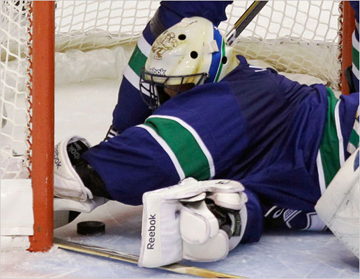 A close look at Canucks goalie Roberto Luongo reaching to pull the puck back across the goal line after a goal by Brad Marchand in the second period.