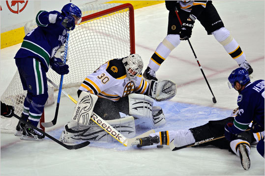 Tim Thomas made a save with a group of players in front of the net in the first period.